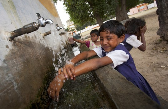 Indian schoolchildren washing at village school
