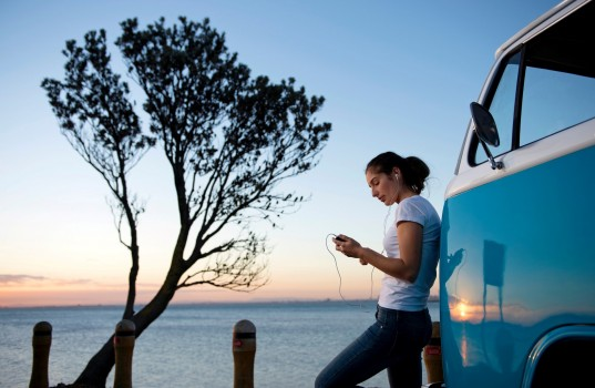 Young woman leaning on camper van at dusk