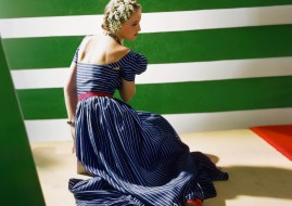 Model from behind wearing a flounced dress of blue foulard, striped like man's tie, and also blue beads, red belt, and red slippers, with green-and-white background *** Local Caption ***