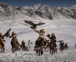 QINGHE, XINJIANG, CHINA - JANUARY 30:  Chinese Kazakh eagle hunters ride with their eagles during a local competition on January 30, 2015 in the mountains of Qinghe County, Xinjiang, northwestern China. The festival, organised by the local hunting community, is part of an effort to promote and grow traditional hunting practices for new generations in the mountainous region of western China that borders Kazakhstan, Russia and Mongolia. The training and handling of the large birds of prey follows a strict set of ancient rules that Kazakh eagle hunters are preserving for future generations.  (Photo by Kevin Frayer/Getty Images)