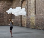 Woman in warehouse, cloud of balloons above head