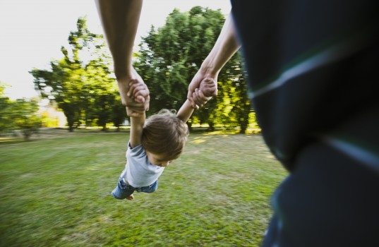 Father spinning little boy in park, cropped