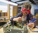 Girl goggles assembling electronics circuit at science center